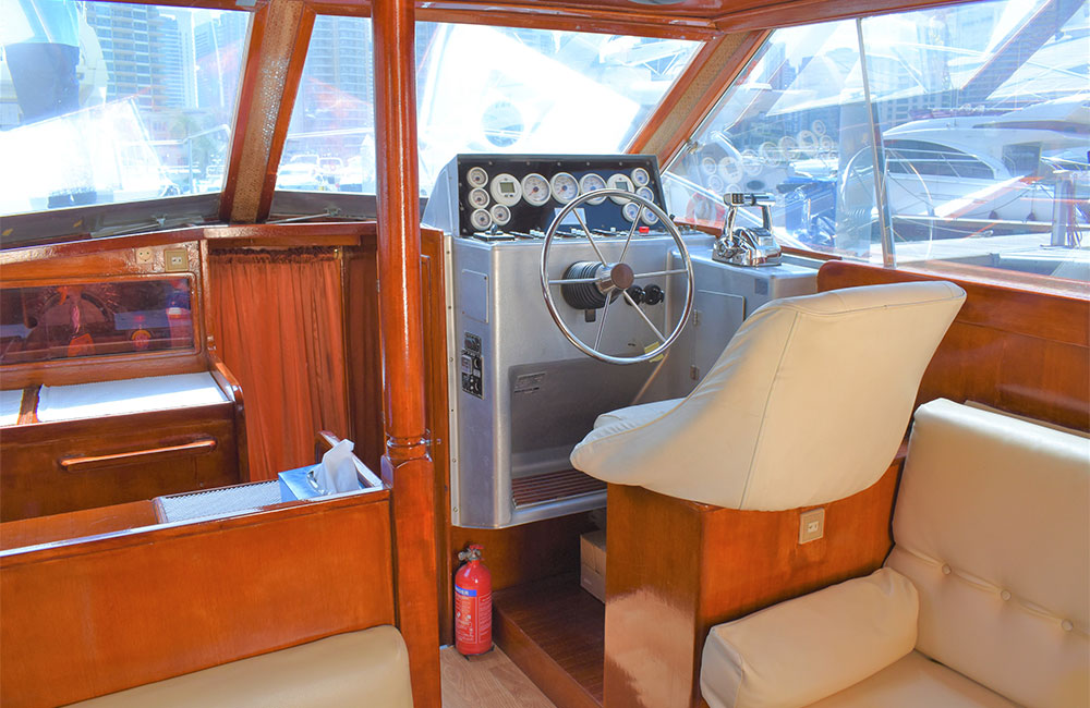 Luxury Yacht having inside control station with classic boat steering wheel finishes look with cozy leather seats