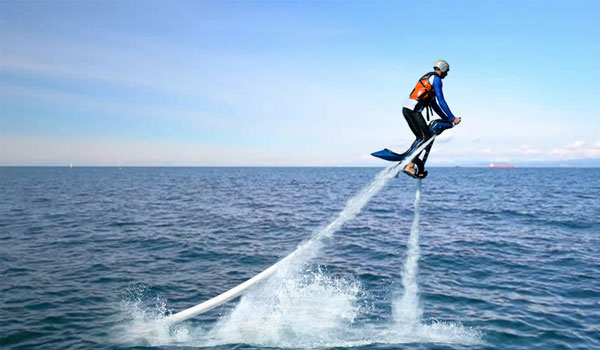 Boy flying like a superhero with flyboard watersports in Dubai